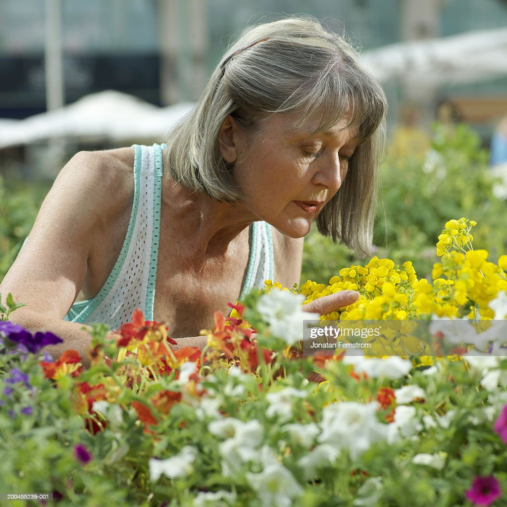 mature woman smelling flowers in outdoor market stock photo | getty