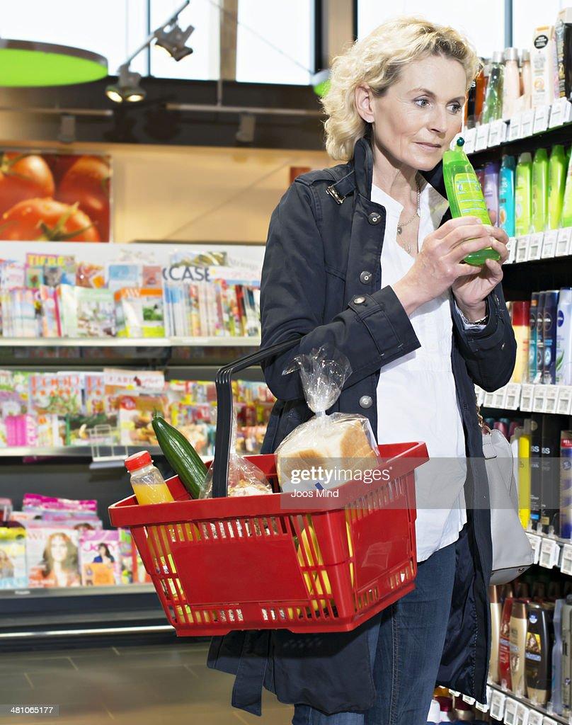 mature woman smelling shampoo insupermarket : Foto de stock