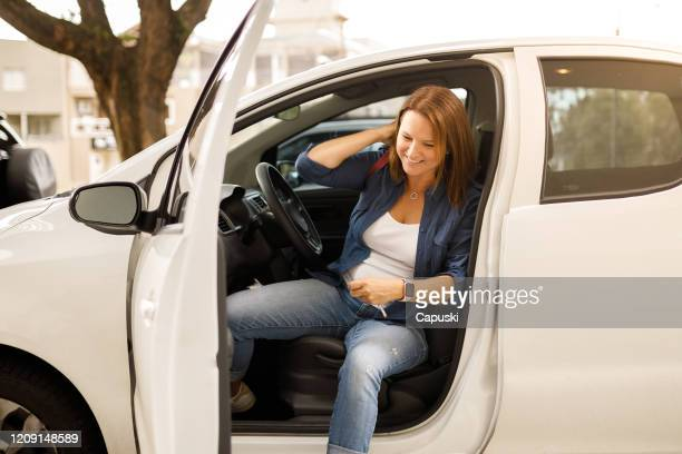 mature woman smiling and leaving the car - disembarking stock pictures, royalty-free photos & images