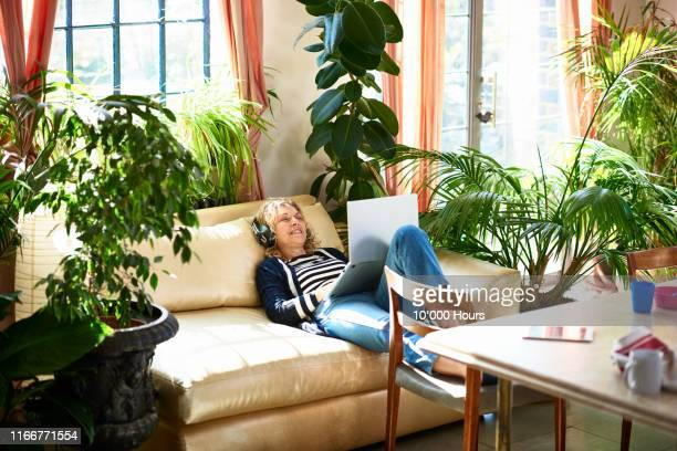 mature woman smiling and relaxing on sofa with headphones - individuality stock pictures, royalty-free photos & images