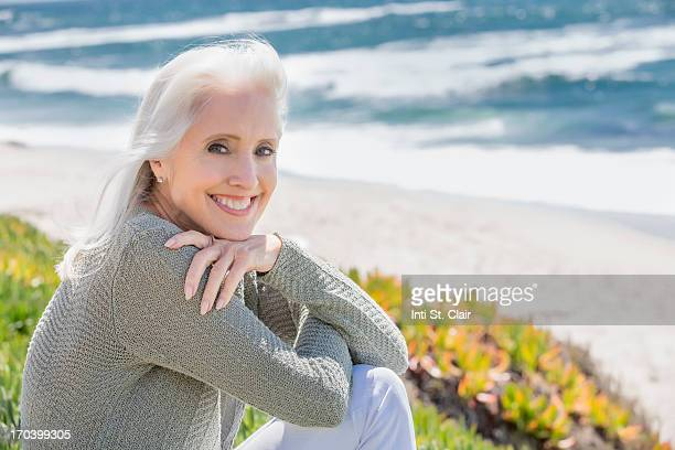mature woman smiling at beach with arms crossed - one mature woman only stock pictures, royalty-free photos & images
