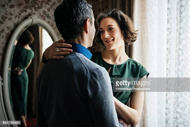 mature woman smiling at her partner in hotel room - green dress stock pictures, royalty-free photos & images