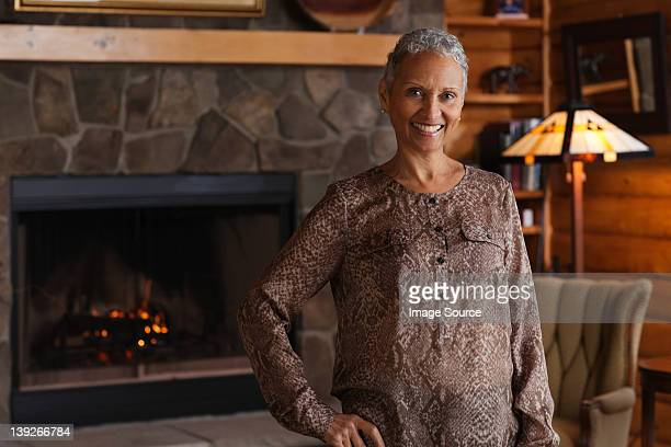 mature woman smiling by fireplace, portrait - hot older women stock pictures, royalty-free photos & images