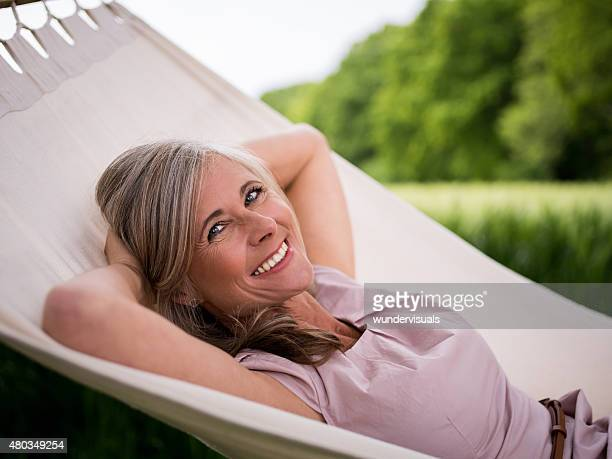 Mature woman smiling happily in a hammock outdoors