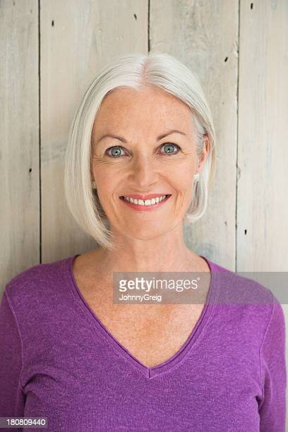 a mature woman smiling in front of a wooden wall. - gray eyes stock pictures, royalty-free photos & images
