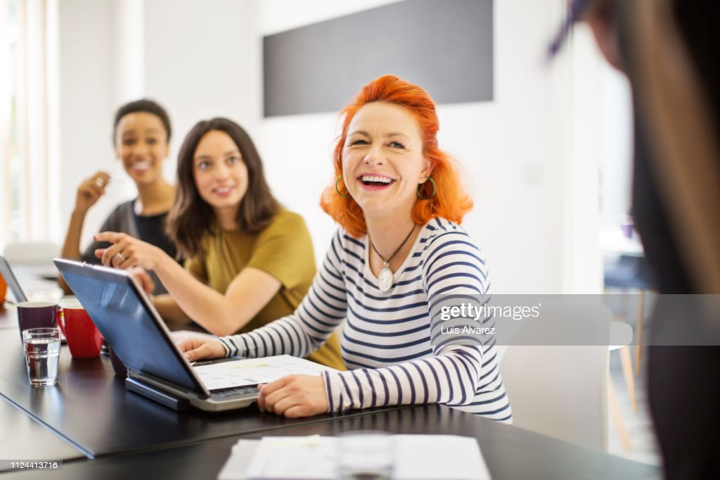 Mature woman smiling in meeting with colleagues : Stock Photo