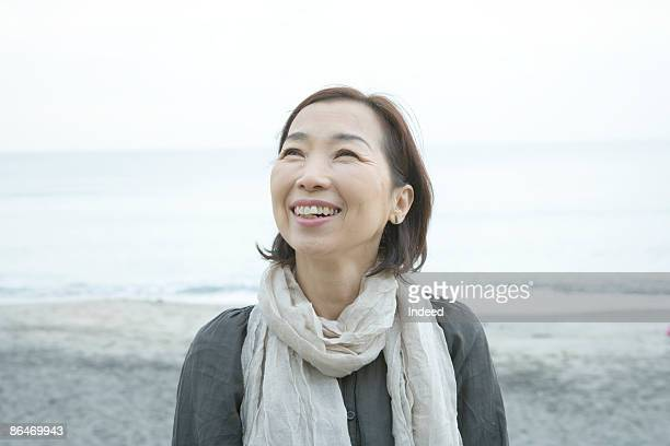 Mature woman smiling, looking up on beach