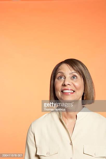 mature woman smiling, looking up - blouse - fotografias e filmes do acervo