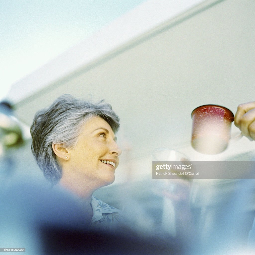 Mature woman smiling, low angle view : Stockfoto