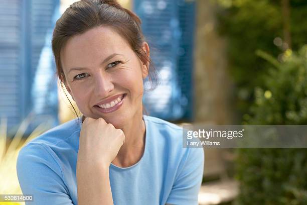 mature woman smiling - hand on chin stock pictures, royalty-free photos & images