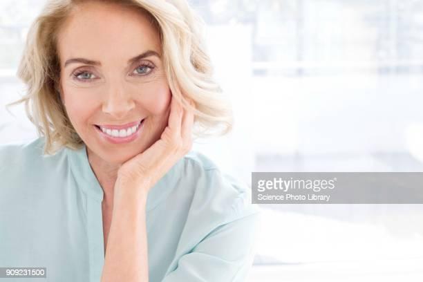 mature woman smiling - kin in de hand stockfoto's en -beelden