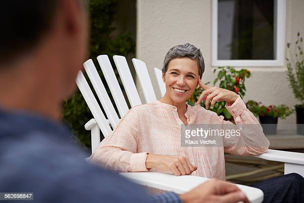 Mature woman smiling to husband sitting across