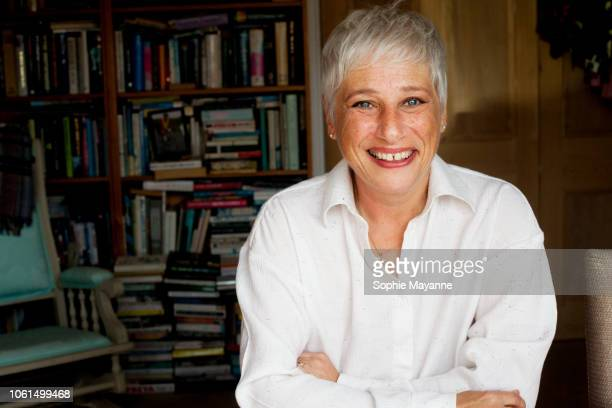 A mature woman smiling with arms folded in front of a bookshelf