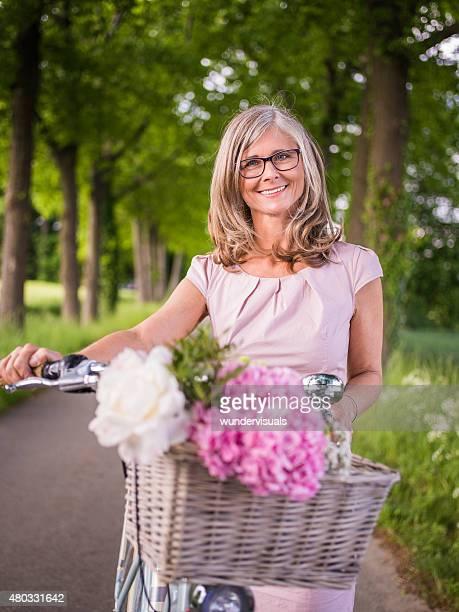 Reife Frau lächelnd mit frischen Blumen und Ihr Fahrrad