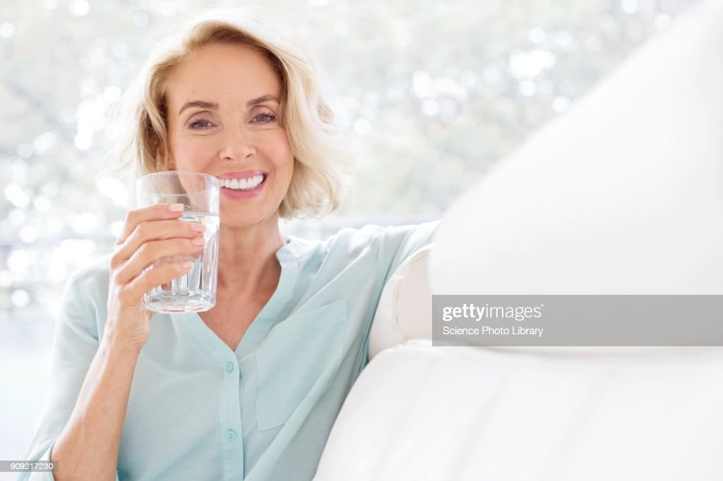 Mature woman smiling with glass of water : Stock Photo