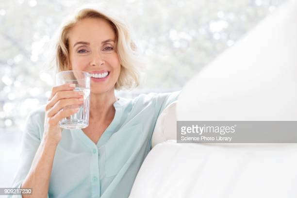 mature woman smiling with glass of water - drinking water stock pictures, royalty-free photos & images