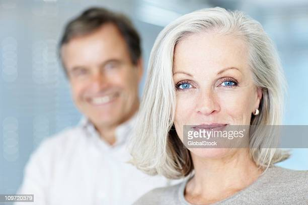 mature woman smiling with man in the background - blue eyes stock pictures, royalty-free photos & images