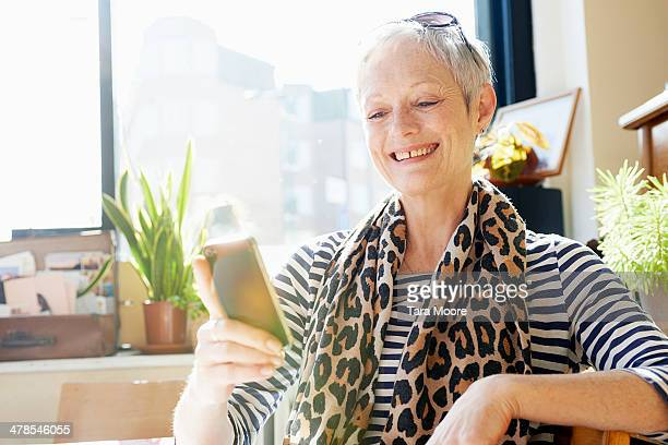 mature woman smiling with mobile