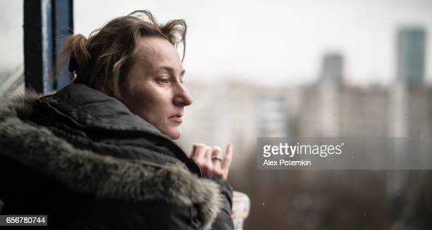 Mature woman smoking and drinking tea on the balcony