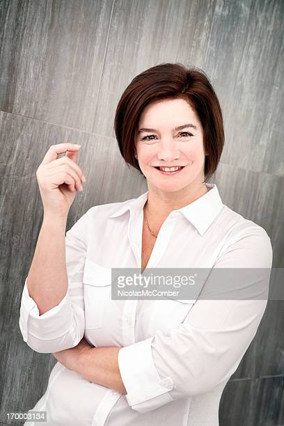 Mature woman snapping fingers in front of tile wall