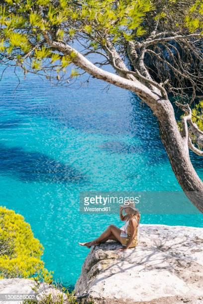 mature woman spending leisure time while sitting on rock by sea - islas baleares fotografías e imágenes de stock