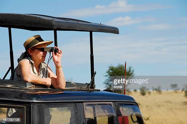 Mature woman spotting wildlife with binoculars during wildlife safari