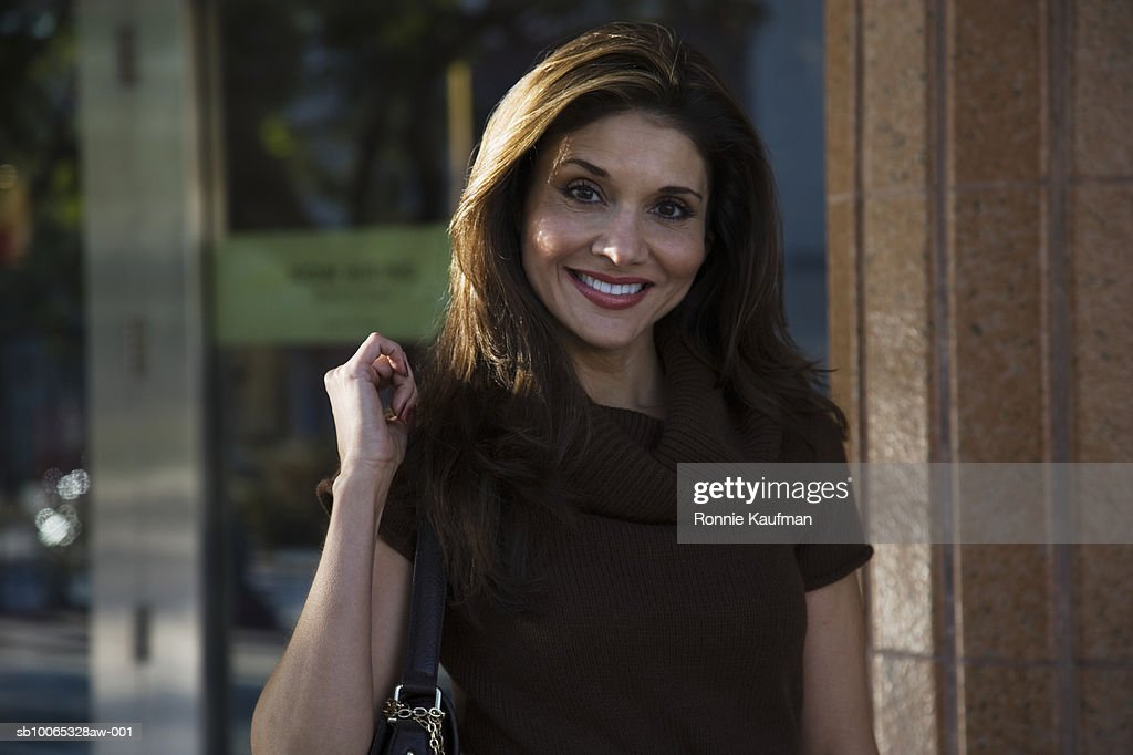 Mature woman standing at door holding handbag, portrait, close-up : Foto stock