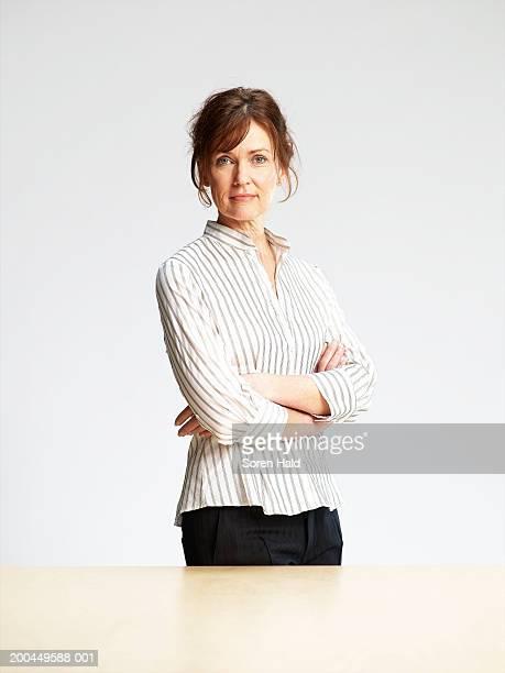 Mature woman standing behind desk, arms folded, portrait