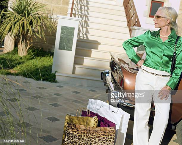mature woman standing by car with shopping bags, hand on hip - satin pants stock pictures, royalty-free photos & images