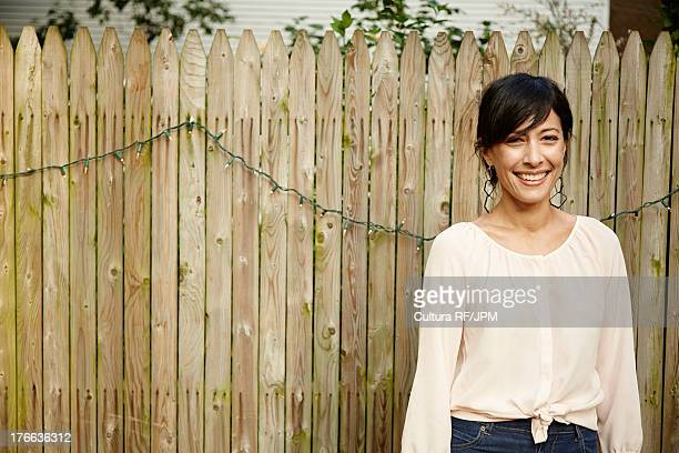 Mature woman standing by garden fence smiling, portrait