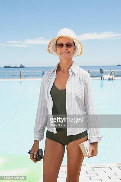 Mature woman standing by pool, wearing sun hat and glasses, smiling