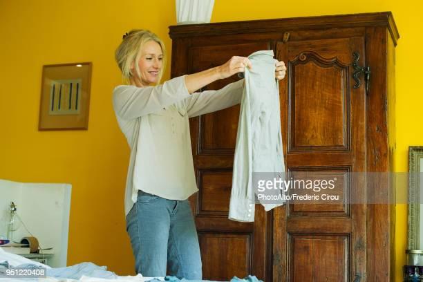mature woman standing in bedroom, holding out shirt - capo di vestiario foto e immagini stock