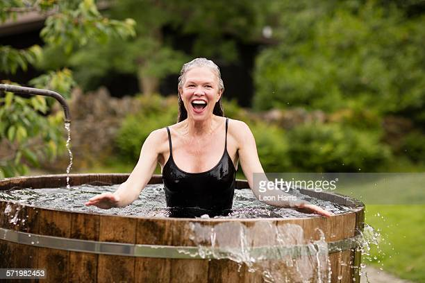 Mature woman standing in fresh cold water tub at eco retreat