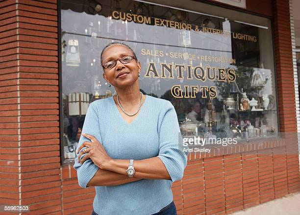 Mature woman standing in front of antique shop
