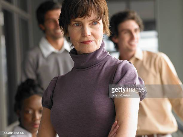 mature woman standing in front of young men and woman, close up - purple shirt stock photos and pictures