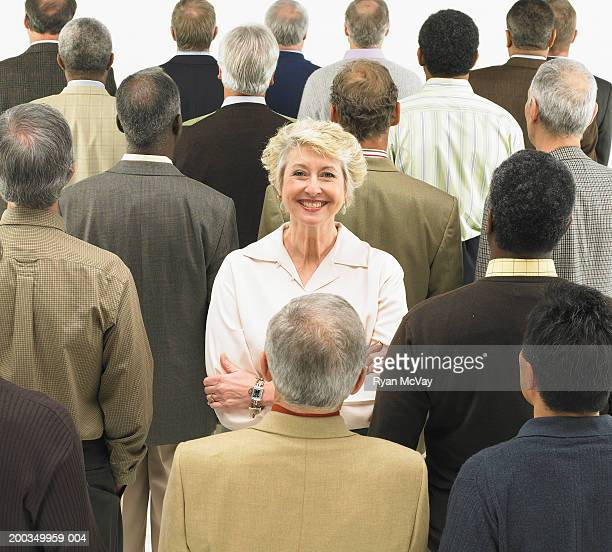 Mature woman standing in group of men with backs turned, smiling