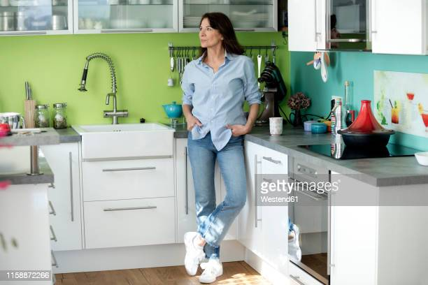 mature woman standing in kitchen at home - stay at home mother stock pictures, royalty-free photos & images