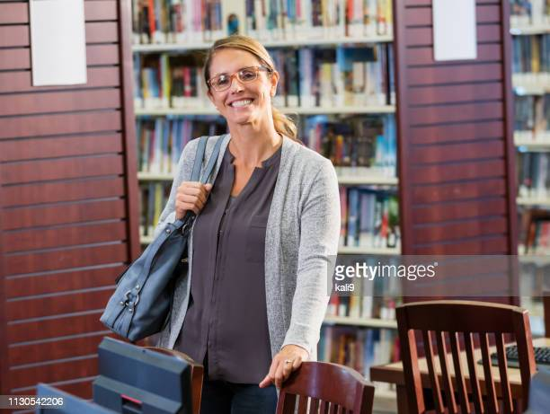 mature woman standing in library - shoulder bag stock pictures, royalty-free photos & images