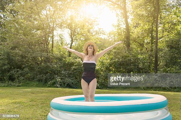 Mature woman standing in paddling pool, arms outstretched
