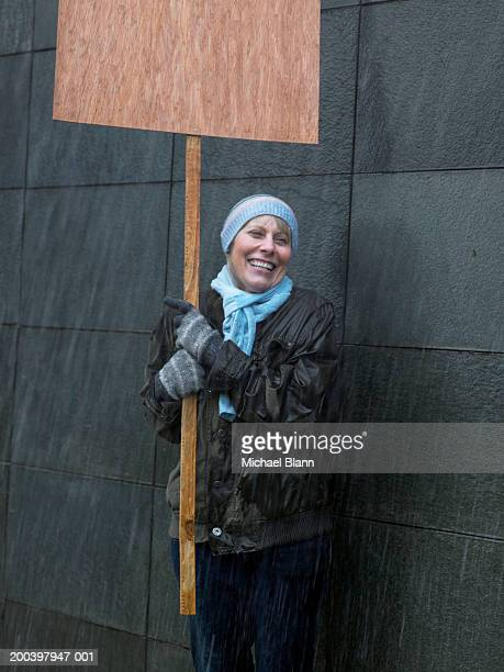 mature woman standing in rain holding placard, looking away, laughing - aktivist stock-fotos und bilder