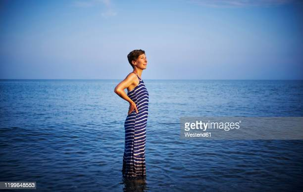 mature woman standing in the sea watching sunset, italy - striped dress stock pictures, royalty-free photos & images