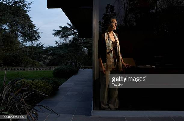 Mature woman standing in window