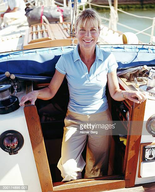 Mature woman standing in yacht hatch, smiling, portrait