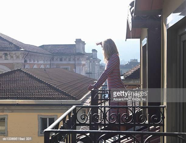 Mature woman standing on balcony