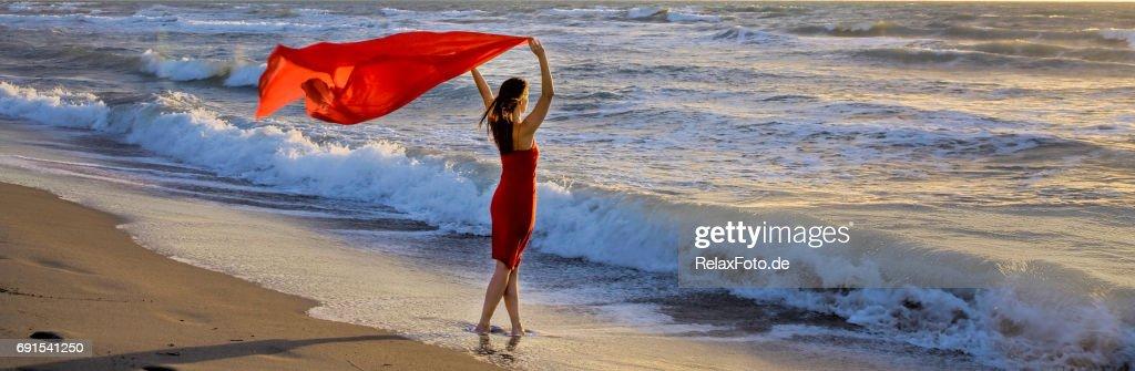 Mujer madura de pie en la playa del Mediterráneo sosteniendo la bufanda roja en el viento : Foto de stock