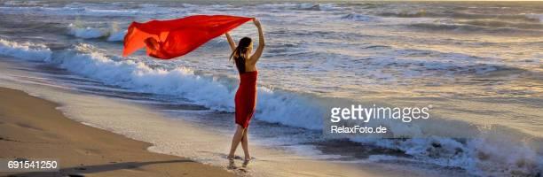 mujer madura de pie en la playa del mediterráneo sosteniendo la bufanda roja en el viento - pañuelo fotografías e imágenes de stock