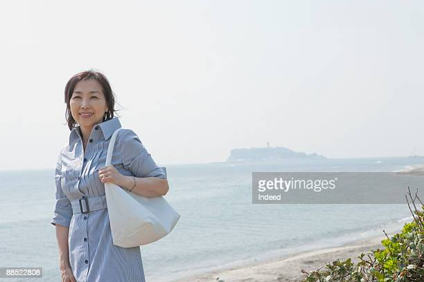mature woman standing on beach - shoulder bag stock pictures, royalty-free photos & images