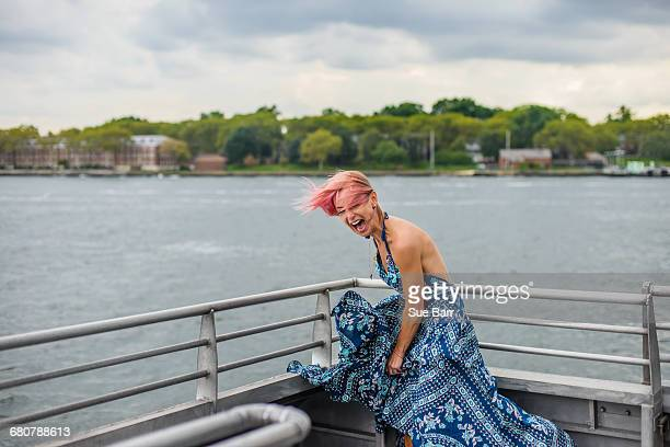 mature woman standing on boat, laughing, wind blowing dress - maxi dress stock pictures, royalty-free photos & images