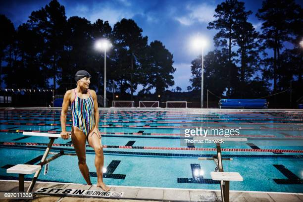 Mature woman standing on deck of outdoor pool before early morning workout