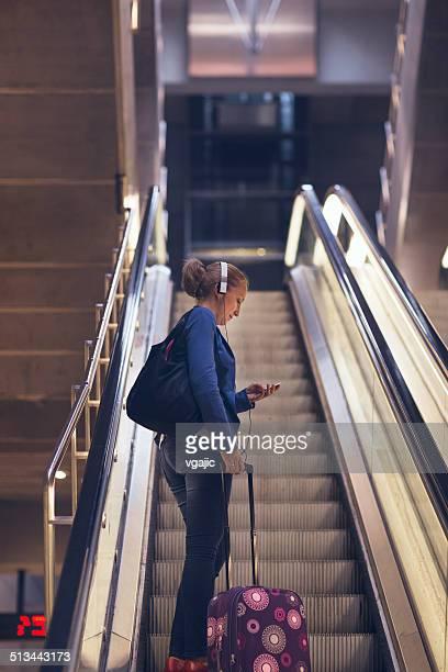 Mature femme debout avec les bagages sur Escalaltor.